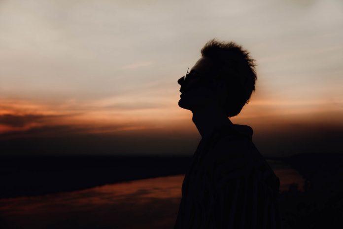 silhouette of man enjoying nature at dusk