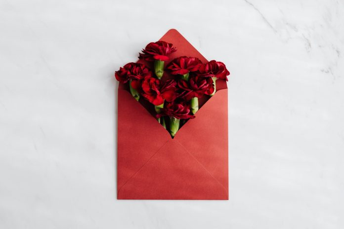 red envelope with fresh red flowers inside