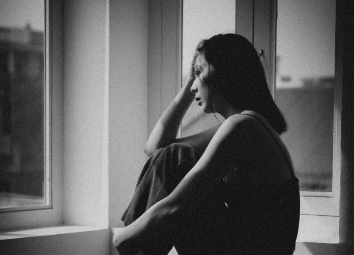 depressed asian woman in corner