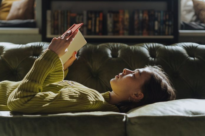 woman in yellow long sleeve shirt lying on couch