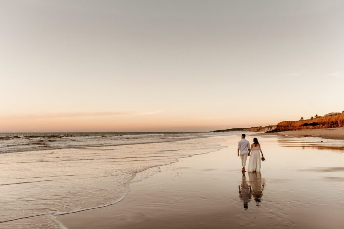 couple in wedding wear walking along seashore