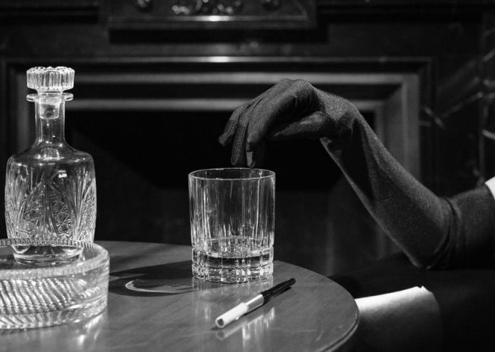 monochrome photo of woman s fingers on the edge of drinking glass